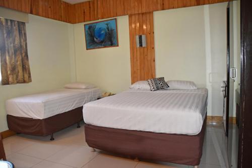 Кровать или кровати в номере Grand Melanesian Hotel