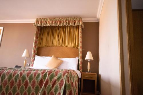 A bed or beds in a room at The Telford Whitehouse Hotel