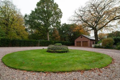 A garden outside Luxury Coach house next to woodland in Knutsford