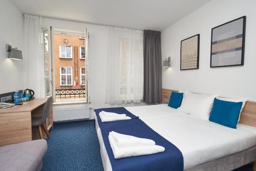 Un ou plusieurs lits dans un hébergement de l'établissement Fama Residence Gdańsk Old Town