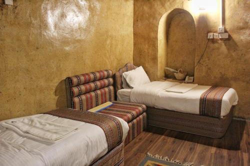 A bed or beds in a room at Nizwa Heritage Inn