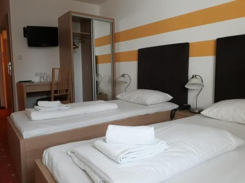 A bed or beds in a room at Lenas Donau Hotel