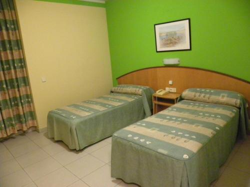 A bed or beds in a room at Hostal Las Fuentes