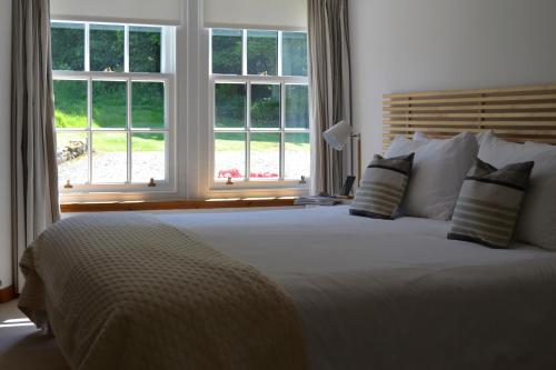 A bed or beds in a room at Balmungo Cottage B&B