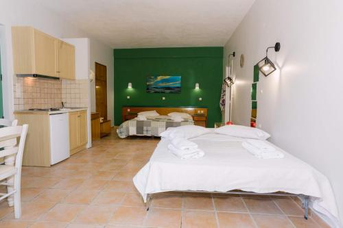 A bed or beds in a room at Rouda Bay Beach Hotel