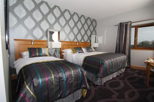 A bed or beds in a room at Errigal Country House Hotel