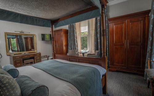 A bed or beds in a room at Skeabost House Hotel