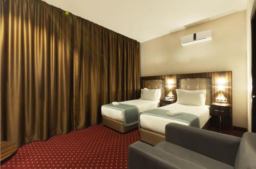 A bed or beds in a room at Legend Business Hotel Batumi