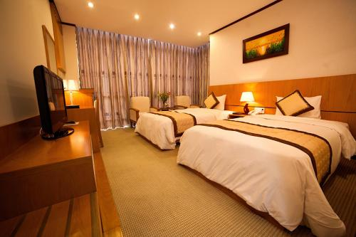 A bed or beds in a room at Danang Petro Hotel