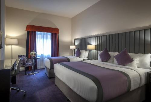 A bed or beds in a room at Trinity City Hotel