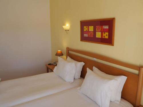 A bed or beds in a room at Luz Bay Hotel