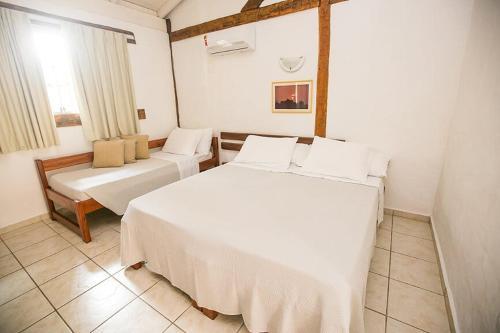 A bed or beds in a room at Pousada Tambayba