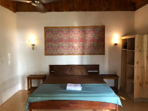A bed or beds in a room at Kambuna Bungalow