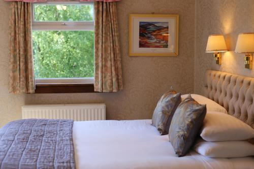 A bed or beds in a room at Pitlochry Dundarach Hotel