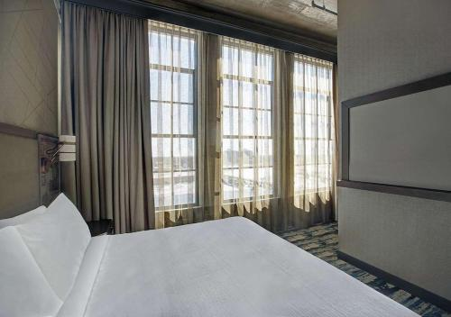 A bed or beds in a room at Embassy Suites By Hilton Rockford Riverfront