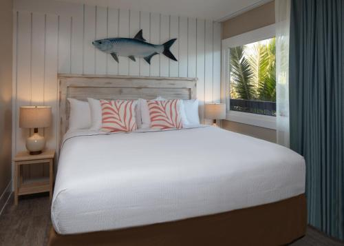 A bed or beds in a room at Postcard Inn Beach Resort & Marina