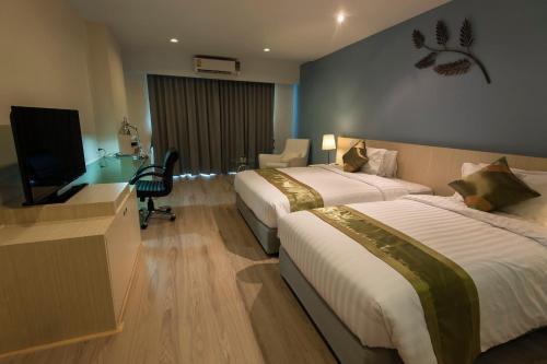 เตียงในห้องที่ โรงแรมแทมมารินด์ การ์เด้นท์