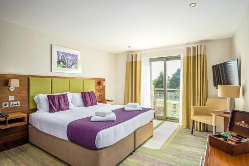 A bed or beds in a room at Cotswolds Hotel & Spa