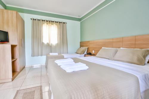 A bed or beds in a room at Pousada Recanto do Amanhecer