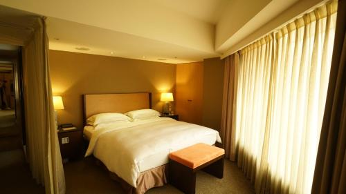 A bed or beds in a room at City Suites - Taipei Nanxi