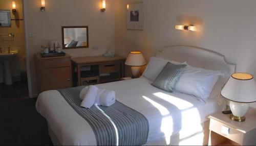 A bed or beds in a room at Lynford Hall Hotel