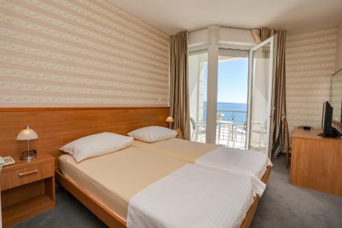En eller flere senge i et værelse på Hotel Neva