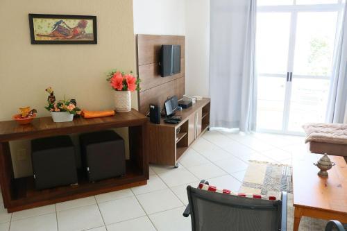 A television and/or entertainment centre at Lindo apartamento de 3 quartos em Jurerê Florianópolis, ideal para famílias