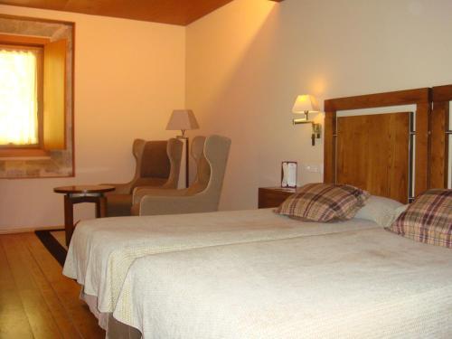 A bed or beds in a room at Parador de Santo Estevo