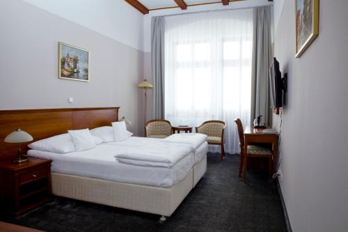 A bed or beds in a room at Wellness Hotel Ida