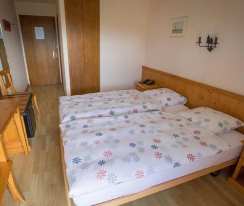 Un ou plusieurs lits dans un hébergement de l'établissement Hôtel Restaurant le Gruyérien