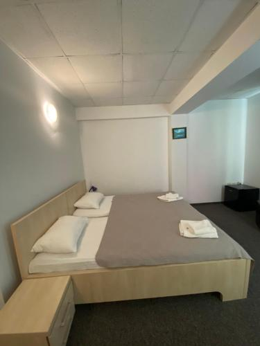 A bed or beds in a room at Pensiunea Ambasador