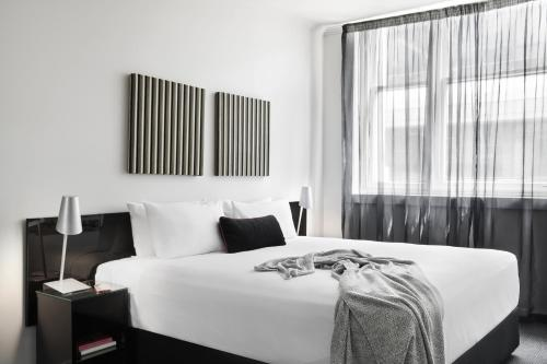A bed or beds in a room at Punthill Apartment Hotel - Flinders Lane