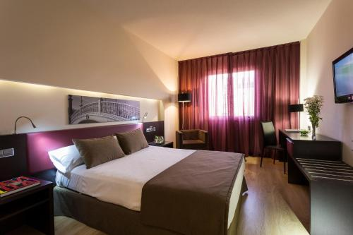 A bed or beds in a room at Ayre Hotel Sevilla