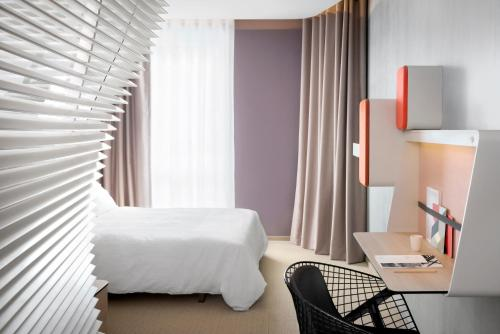 A bed or beds in a room at Okko Hotels Nantes Château