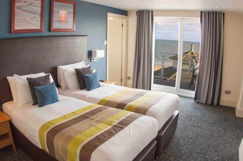 A bed or beds in a room at Sandbanks Hotel