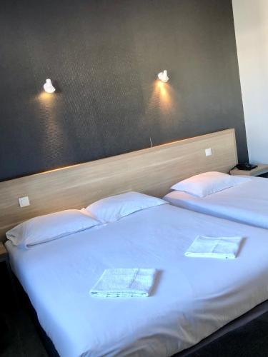 A bed or beds in a room at Hôtel le Bretagne et Restaurant Le Papillon