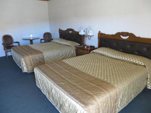 A bed or beds in a room at Alamo Inn