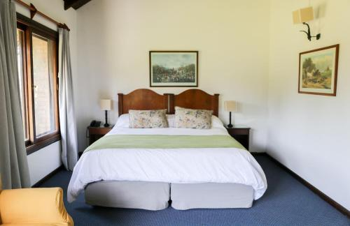 A bed or beds in a room at La Posta del Pilar Hotel & Spa