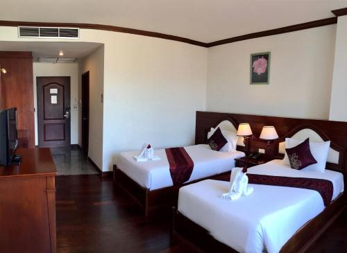 A bed or beds in a room at Arawan Riverside Hotel