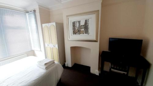 A bed or beds in a room at Priestfield House Medway