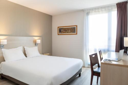 A bed or beds in a room at Aparthotel Adagio Access Avignon