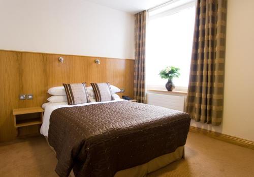 Een bed of bedden in een kamer bij Blooms Hotel