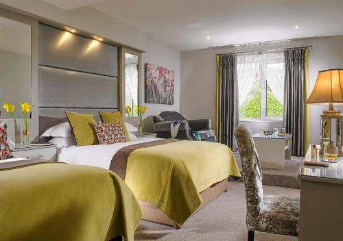 A bed or beds in a room at Fitzgeralds Woodlands House Hotel