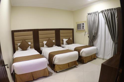 سرير أو أسرّة في غرفة في شقق سوات الفندقية