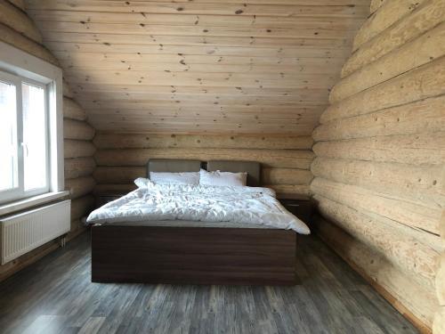 Кровать или кровати в номере Бревенчатый коттедж