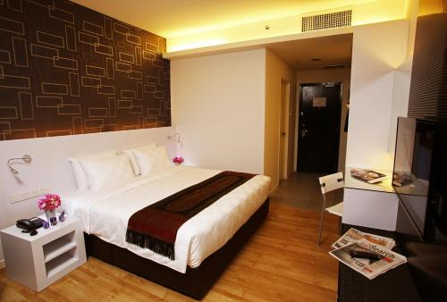 A bed or beds in a room at Cairnhill Hotel Kuala Lumpur