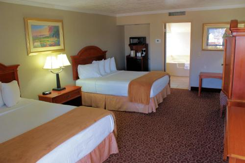 A bed or beds in a room at Red Arrow Inn & Suites