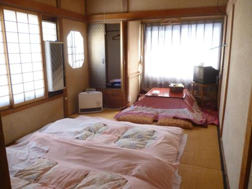 A bed or beds in a room at Uotoshi Ryokan