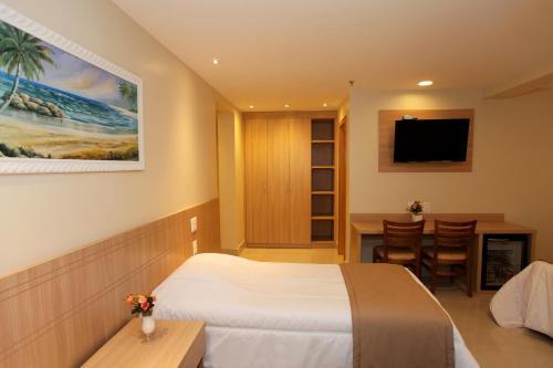Кровать или кровати в номере Elegance Praia Hotel