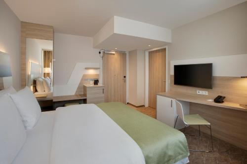 A television and/or entertainment center at Holiday Inn Frankfurt Airport, an IHG Hotel